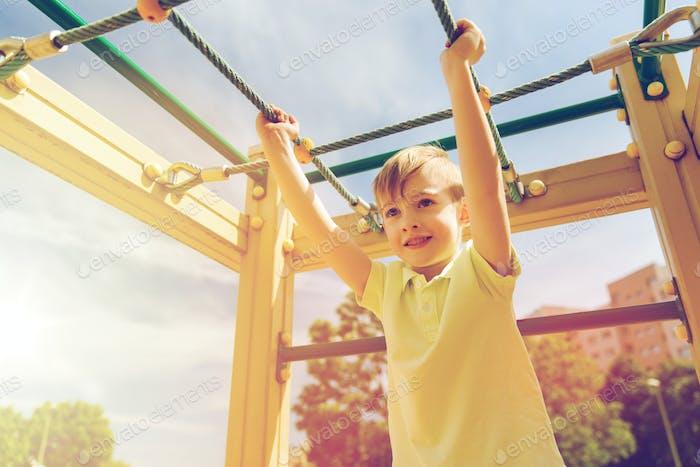 happy little boy climbing on children playground