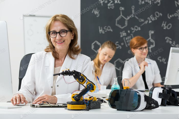 Smiling professor sitting in a classroom