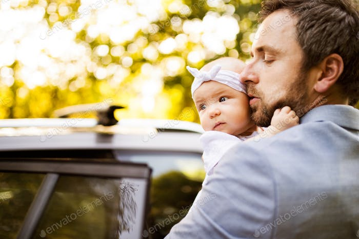 Young father with his little baby girl going into the car.
