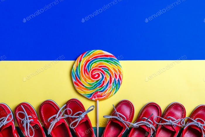 Small red boat shoes near big multi-colored lollipop