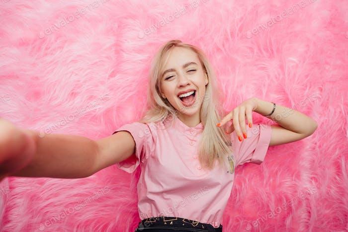 Lustige junge Mädchen Bloggerin in Mode rosa Kleid gekleidet nimmt ein Selfie auf ihrem Smartphone auf der