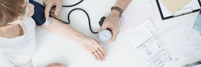 Doctor measuring patient's blood pressure