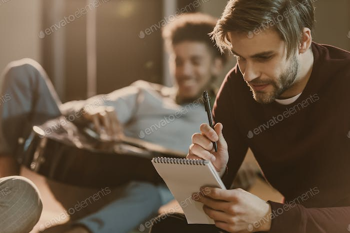 handsome young man writing lyrics in notepad while his friend lying on floor with guitar
