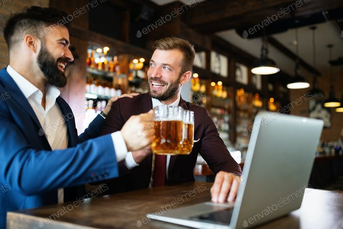 Happy young businessmen in suits are smiling and talking in a restaurant