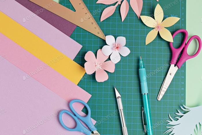 Top view over paper cut tools, scissors, cutter, cutting mat, and crafted paper objects. DIY trendy