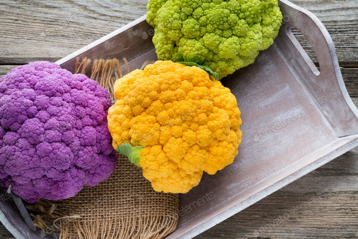 Rainbow of eco cauliflower on the wooden table.