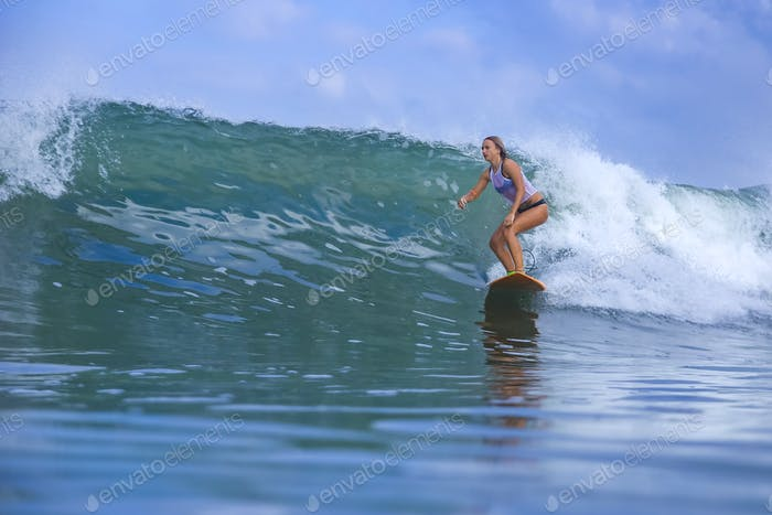 Young woman surfer on a blue wave