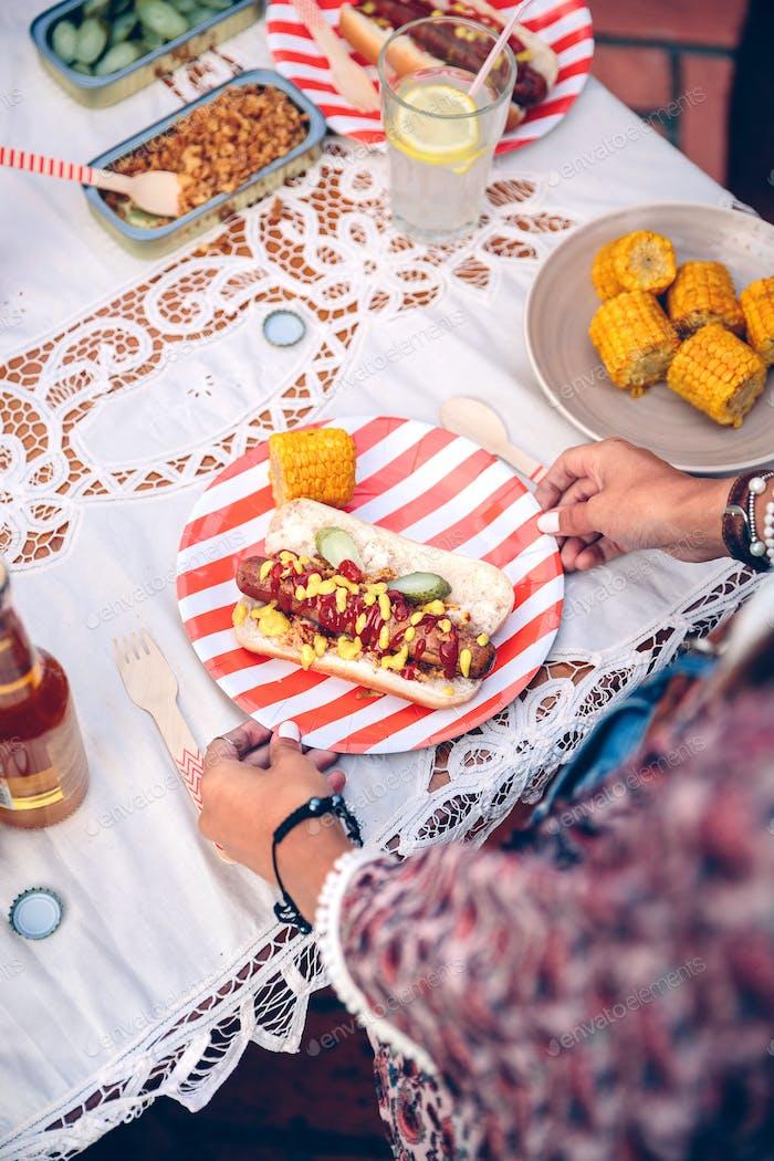 Frau hält Teller mit Hot Dog und Mais