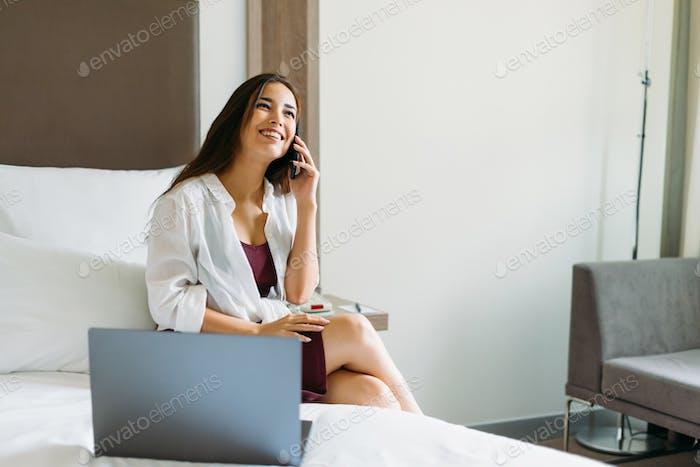 Schöne lächelnde asiatische Mädchen mit langen Haaren sprechen auf Handy mit Laptop auf dem Bett im Hotelzimmer