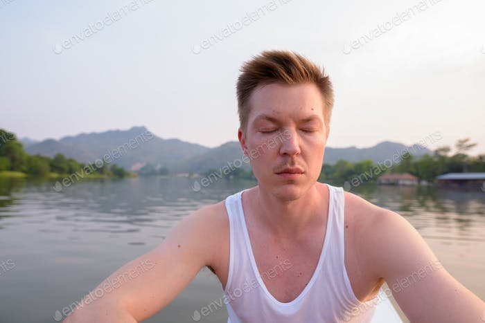 Tourist man sitting in boat while having holiday in Thailand
