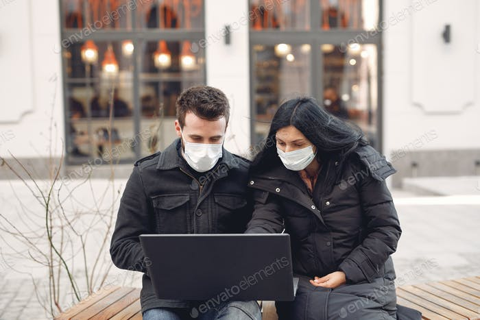 People in a masks sitting in a city with a laptop