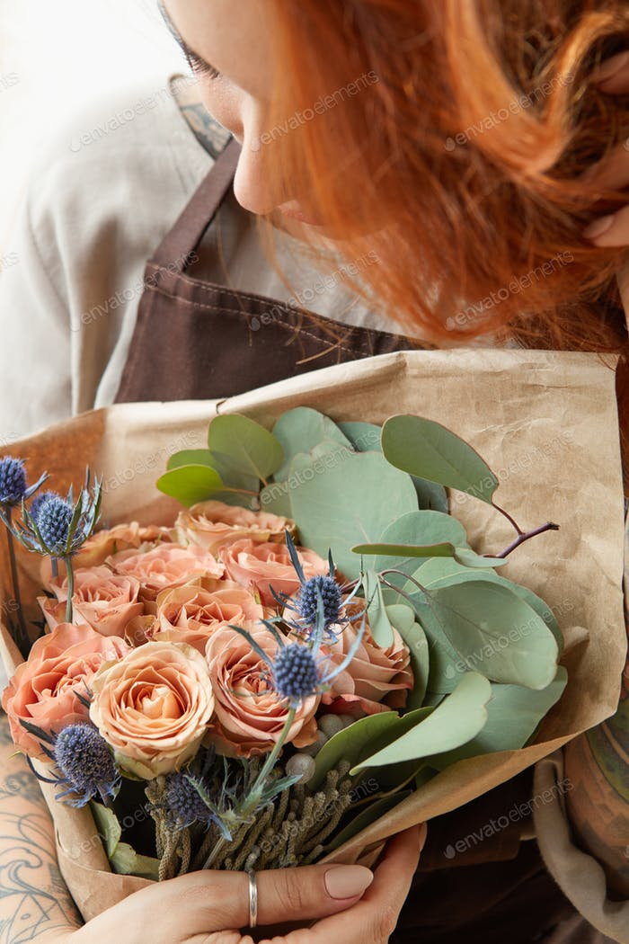 Young girl with red hair holds beautiful bunch of roses living coral colored. Close-up. Conept of