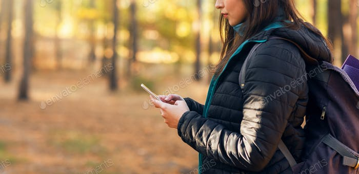 Unrecognizable woman with smartphone at autumn woods