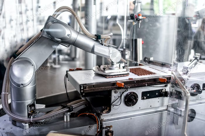 automatic robotic hand moving and preparing tiny bits of chocolate