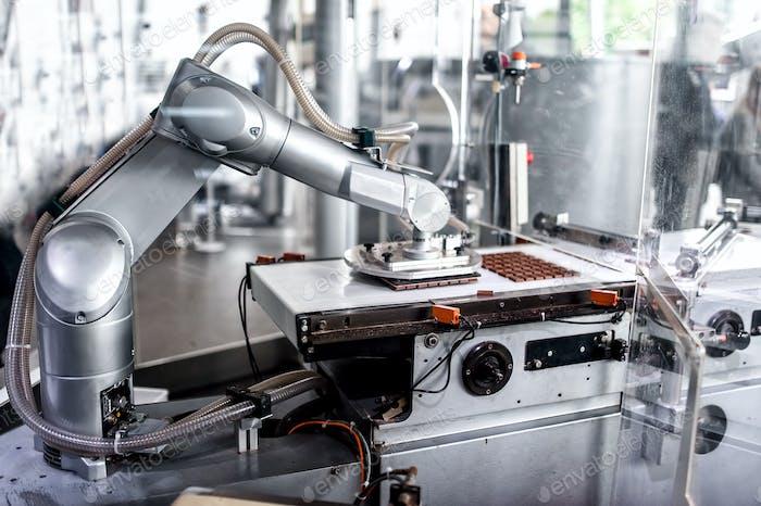 automatische Roboterhand bewegen und vorbereiten winzige Stücke von Schokolade
