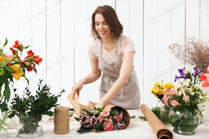 Happy florist woman working with flowers in workshop.