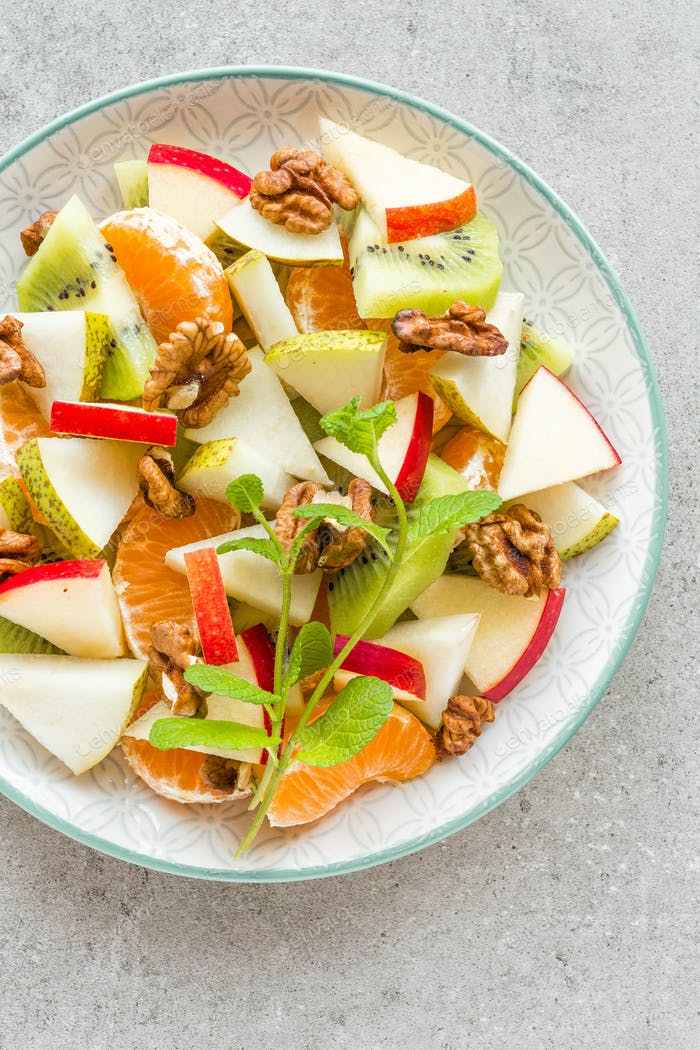 Fruit salad of fresh sweet apple, pear, tangerine and walnuts. Healthy vegetarian food