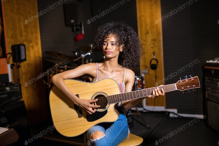 Trendy young black woman playing guitar
