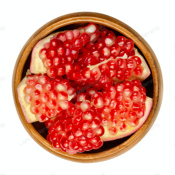 Pomegranate clusters, Punica granatum, in a wooden bowl