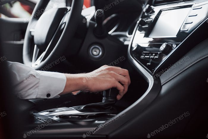 Young man driving a road car holding his hand on a gearbox. A businessman rides on his car