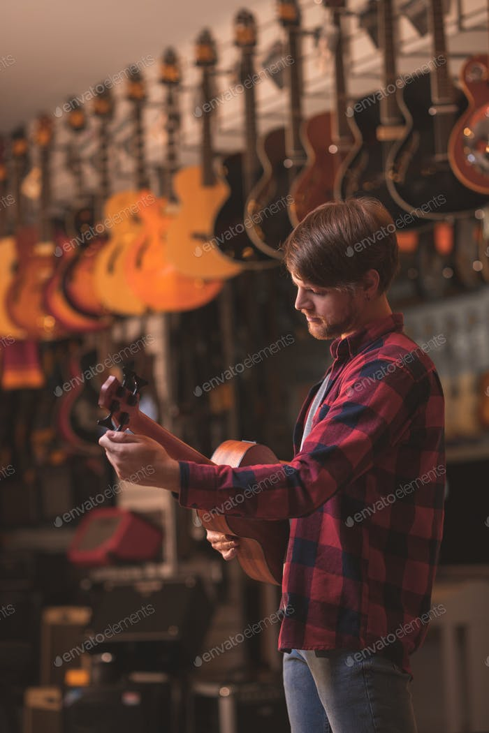 Young man playing on a ukulele in a store
