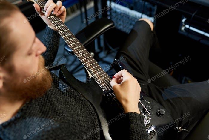 Crop musician playing guitar in studio