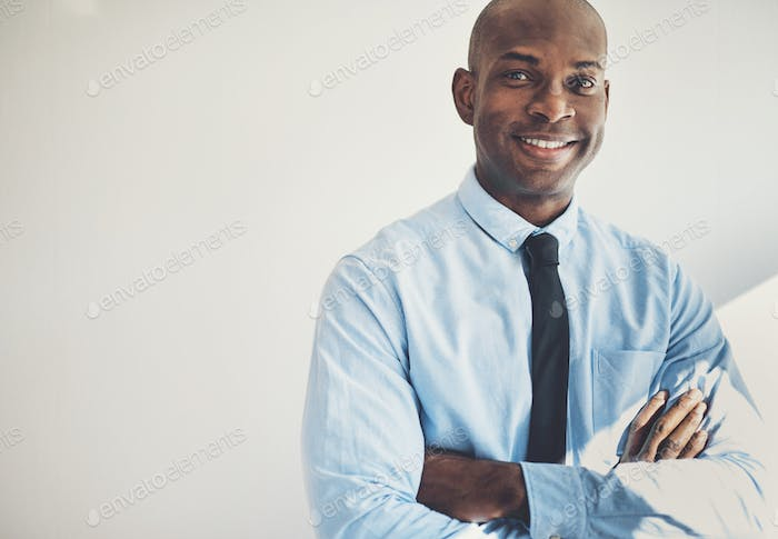 Smiling businessman standing with his arms crossed in an office