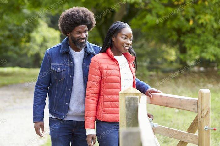 Man opening a gate for his girlfriend during a walk in the country, close up