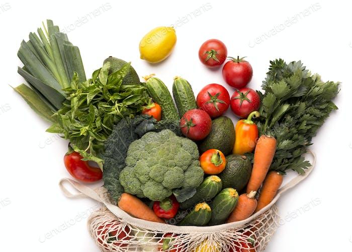 Fresh vegetables from farm inside eco bag on white