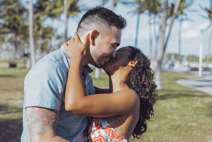 Amorous kissing couple in bright sunshine