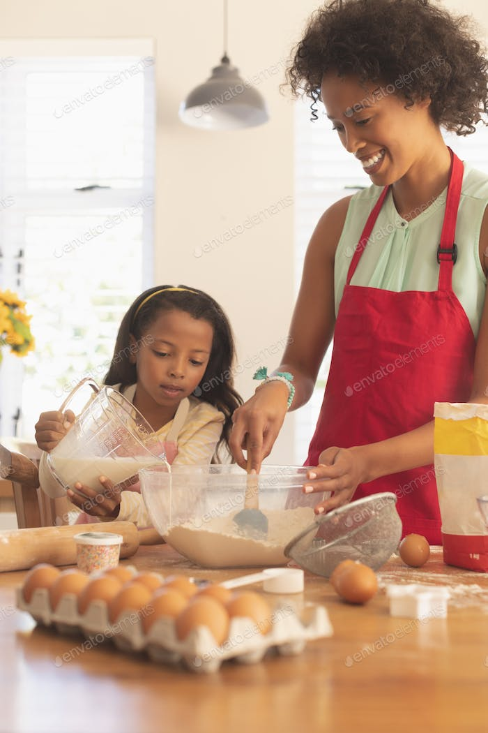 Mother and daughter mixing cookie dough ingredients together in kitchen at homey