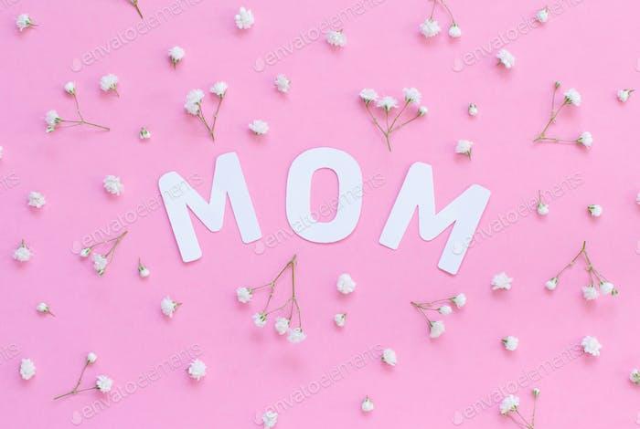 Blumen und Wort MOM auf einem hellrosa Hintergrund