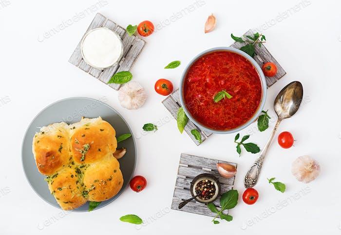 Traditional Ukrainian Russian vegetable borscht soup  on blue bowl. Flat lay. Top view