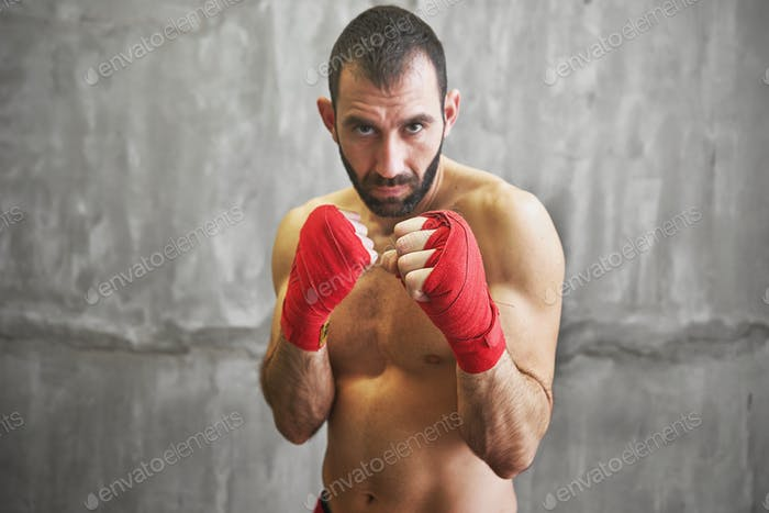 Shot of wrapped hands  with red boxing tape of young boxer fight