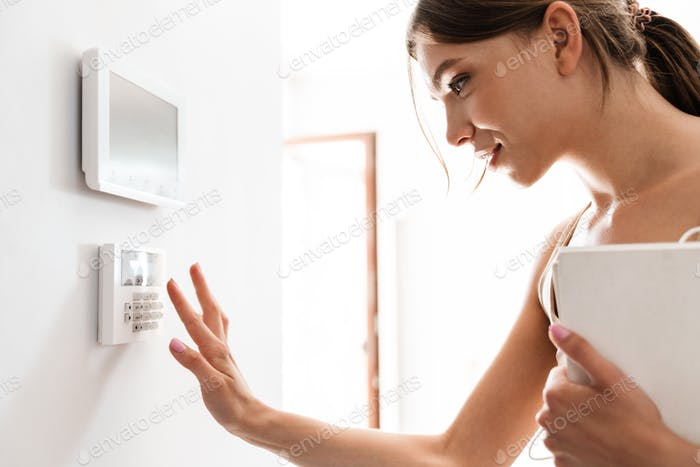 Young woman entering code on keypad of home security alarm