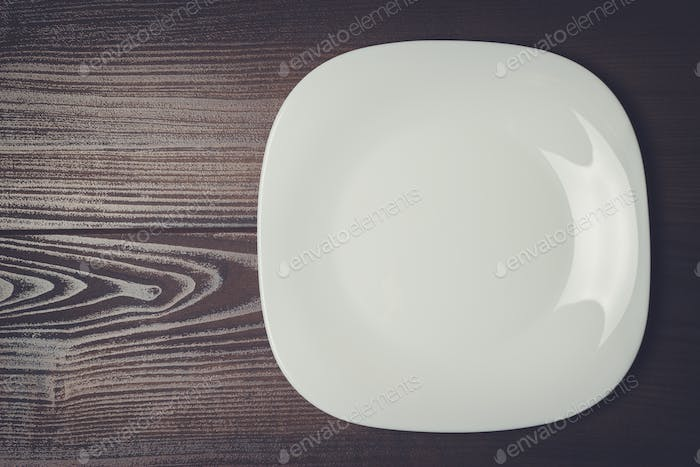 white square plate on the wooden brown table