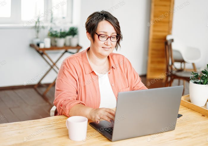 Adult charming brunette woman in glasses plus size body positive working with laptop