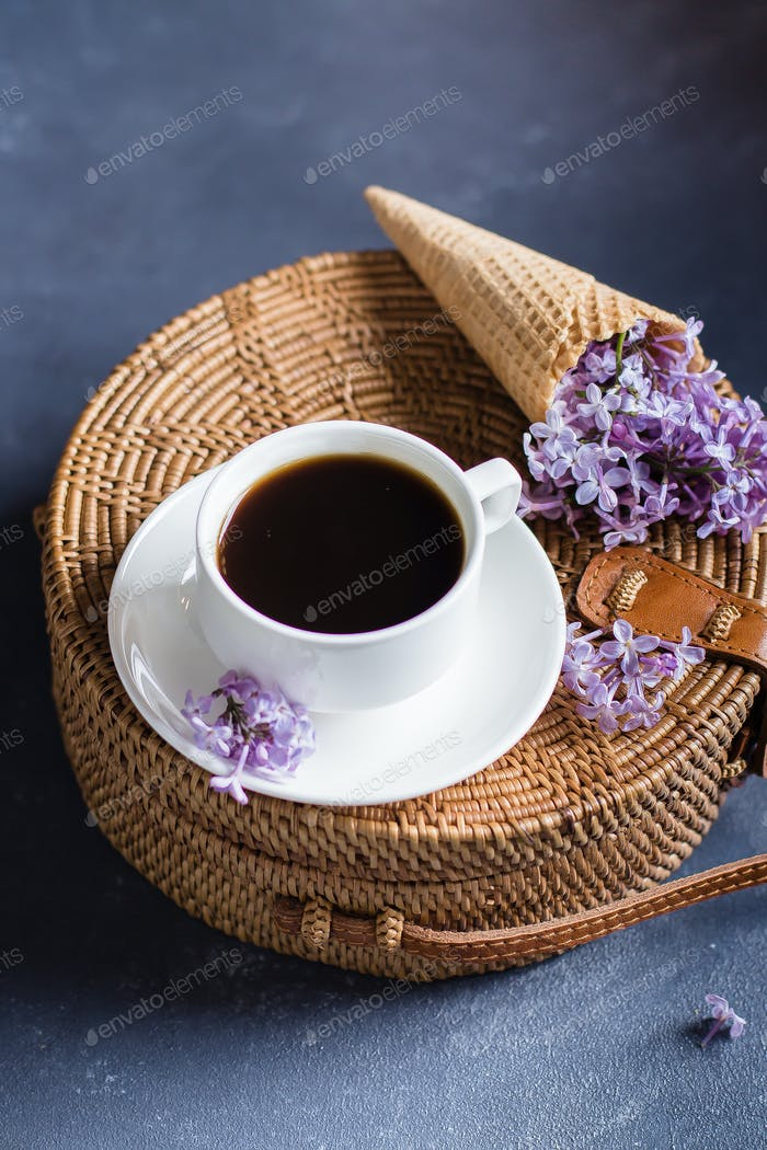 Fashionable rattan bag, cup of coffee and purple lilac in waffle cone. Spring Summer Card Concept