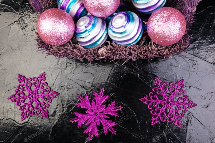 Christmas balls in purple basket on black background. Decorative snowflakes.