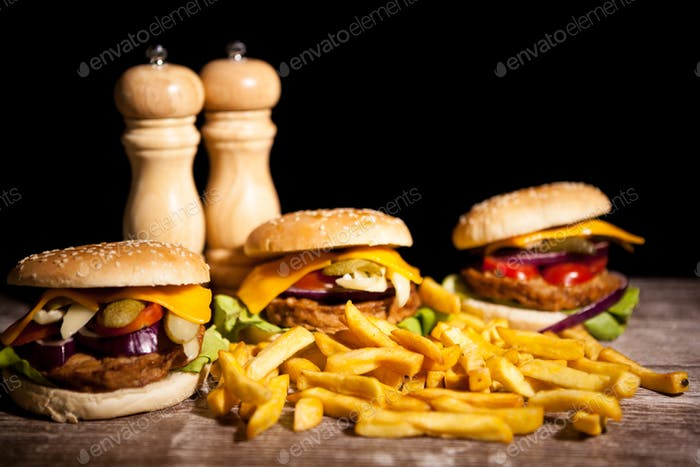 Delicious home made burgers on wooden plate on black background