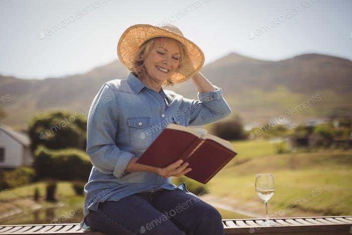 Senior woman reading a book on park bench