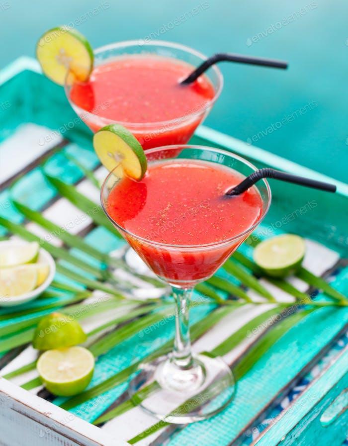 Erdbeere Margarita Cocktail auf buntem Holzhintergrund mit Palmblatt.