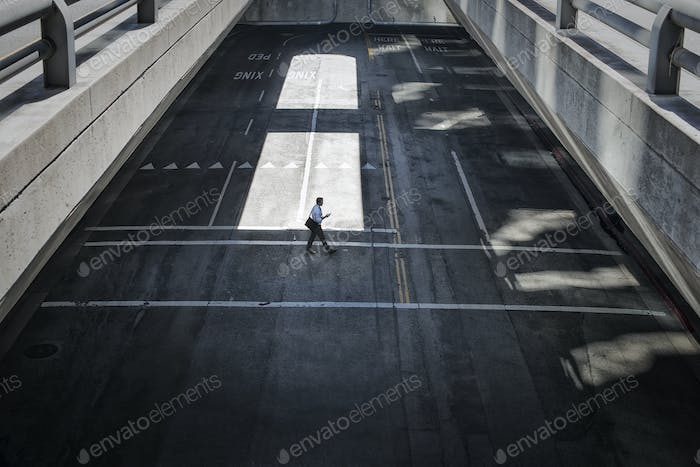 View from above onto a city plaza and two men walking from shadow into sunlight.