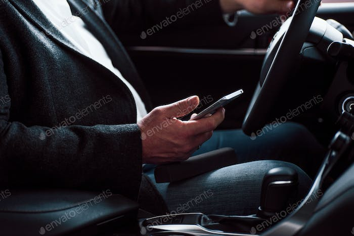 Working in the car using silver colored smartphone. Senior businessman