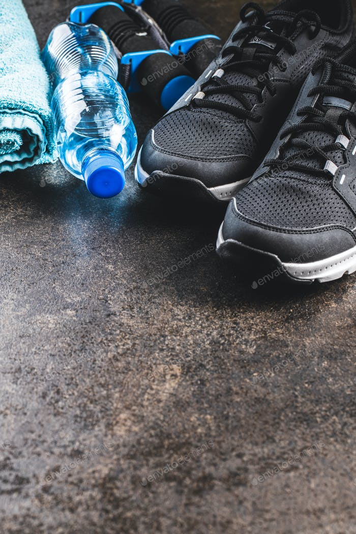 Fitness concept. Black sports shoes, towel, dumbbells and bottle of water.