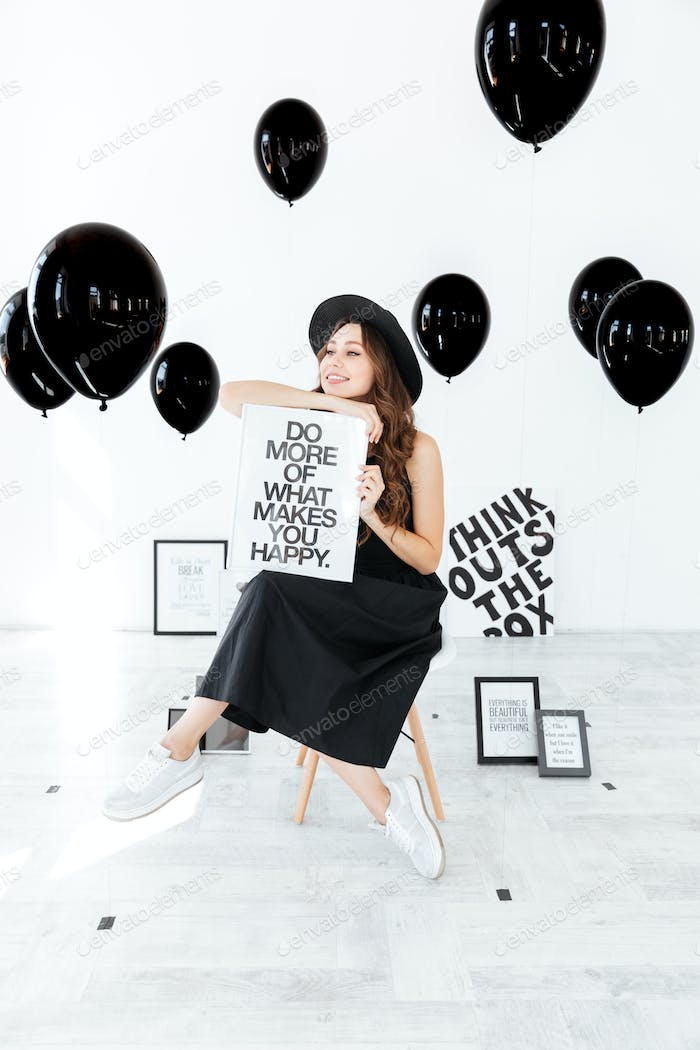 Happy young woman sitting and holding white board