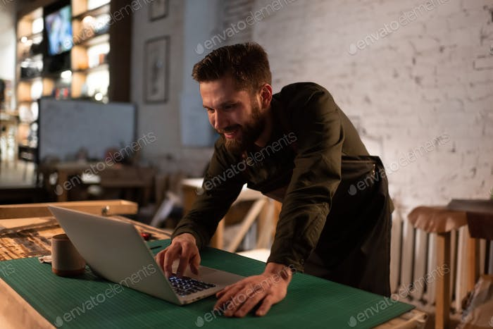Cheerful artisan using laptop in studio