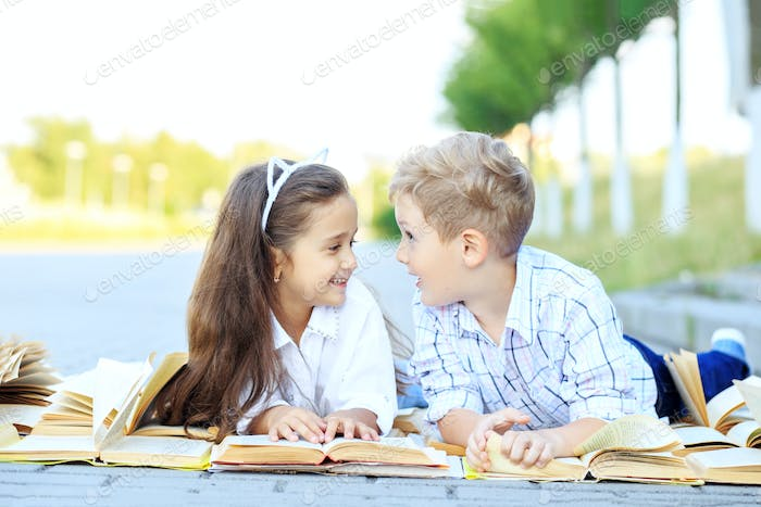Children read, chat and laugh. The concept is back to school, education, reading, friendship
