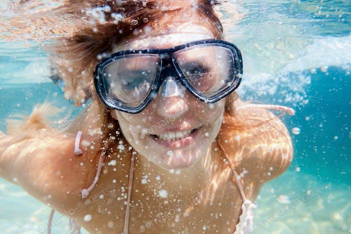 Mujeres buceando en el agua tropical, snorkel con máscara