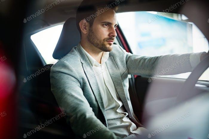 Handsome elegant serious man drives a car
